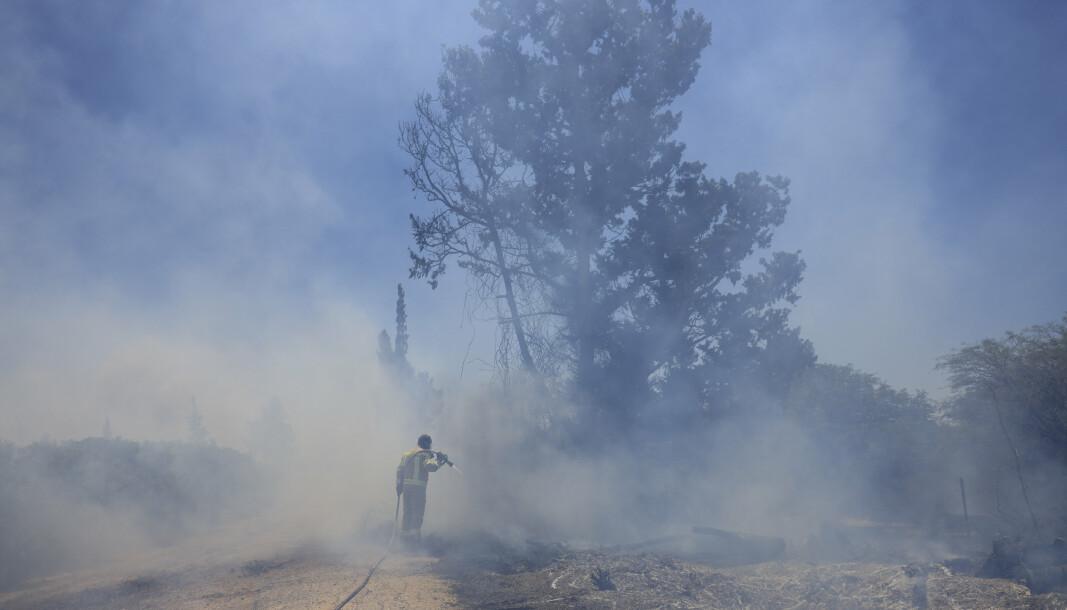 BRANN: En israelsk brannmann forsøker å slukke brannene etter palestinere sendte brannballonger mot grensa mellom Israel og Gaza.