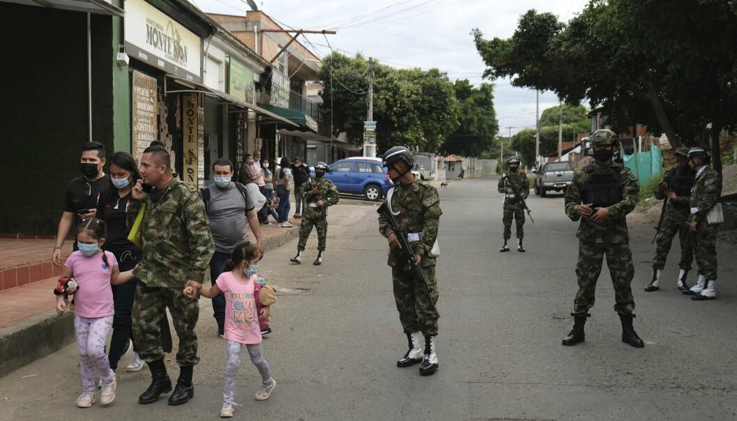 COLOMBIA: En soldat går sammen med familien sin i nærheten av militærbasen som ble rammet av et bombeangrep i Cucuta tirsdag.