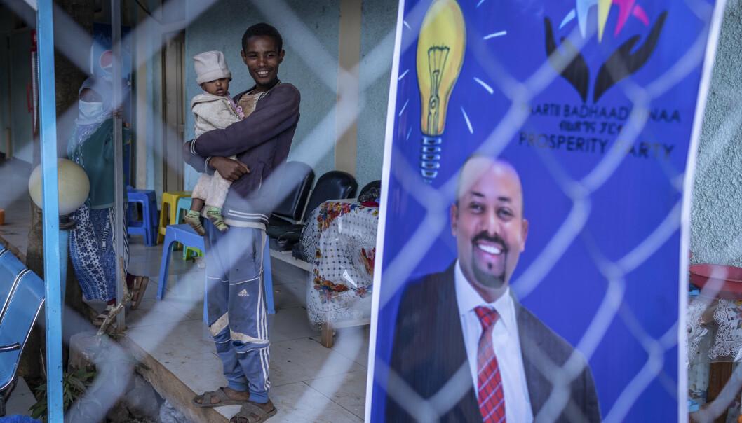 20 år gamle Gezale Abamecha, som har datteren på armen, står ved siden av en valgplakat der Etiopias statsminister Abiy Ahmed ber om fornyet tillit fra velgerne. Mandag holdes det valg på ny nasjonalforsamling i Etiopia, men millioner får ikke delta.