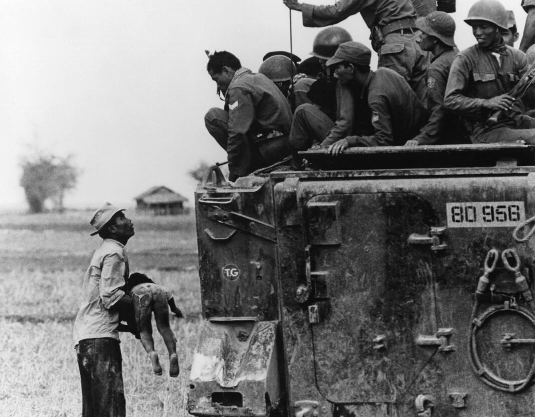 KRIG: En far holder barnet sitt opp mot vietnamesiske soldater under vietnamkrigen 1964.