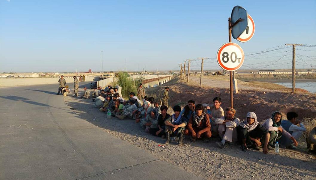 Afghanistans regjeringssoldater sitter ved en bro ved siden av Tadsjikistan-Afghanistan-grensen i Tadsjikistan.