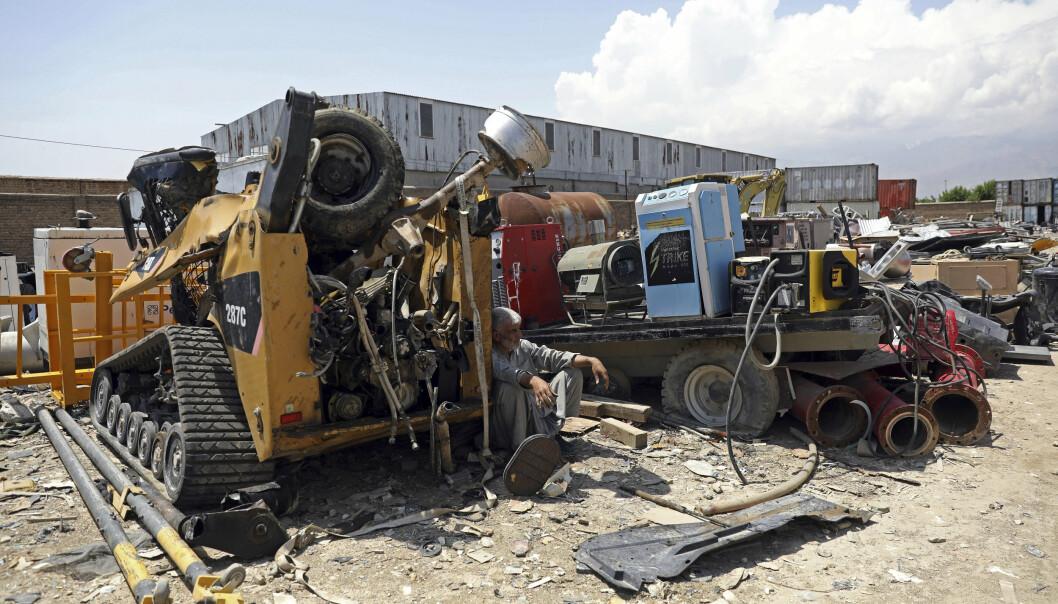 SØPPEL: En mann hviler seg på en amerikansk søppelfylling nær Bagram-basen i starten av mai.