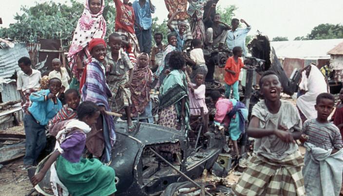 NEDBRENT HELIKOPTER: Unge somaliere sitter på de nedbrente restende av et amerikansk helikopter som styrtet, i oktober 1993, mens de roper slagord for å uttrykke sin motstand mot amerikanerne.