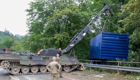 LØFT: En konteiner som ble tatt av flommen fjernes.