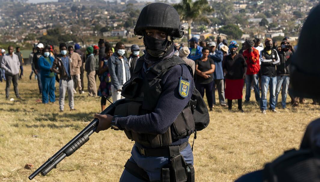 En bevæpnet politimann patruljerer mens politiminister Bheki Cele besøker Phoenix.