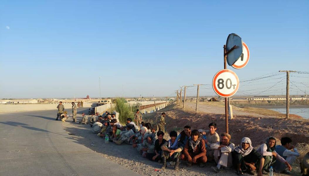 FLYKTET: Afghanske regjeringstyrker sitter på en bro i Tadsjikistan nær den afghanske grensen etter at de måtte flykte fra Taliban.