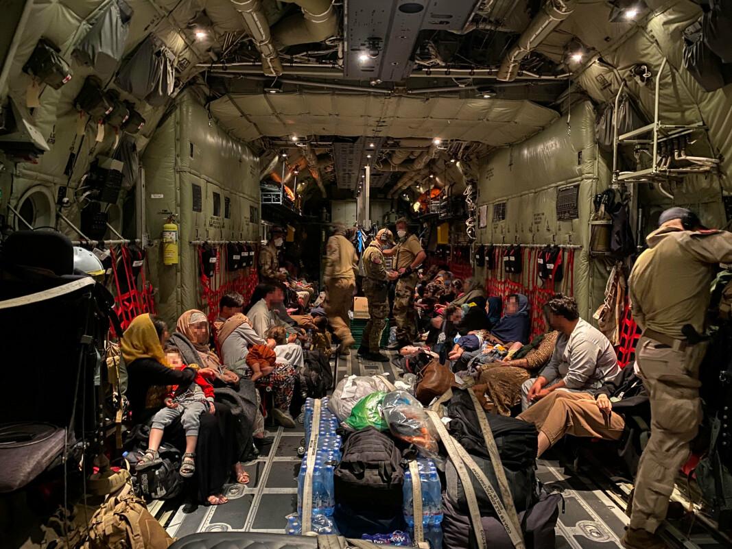 EVAKUERT: Her ser vi lasterommet til det norske C-130 J Hercules transportflyet med sivilt personell fra Kabul . Antall evakuerte har variert for hver tur, opplyser Luftforsvaret. (Personene på bildet et sladdet av Forsvaret).