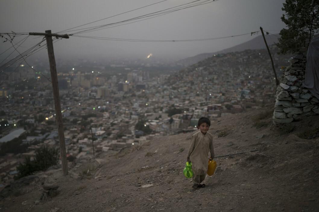 VANN: En liten gutt bærer vann opp til huset der han bor på en topp med utsikt over den afghanske hovedstaden Kabul.