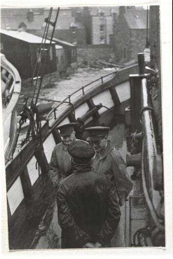 Oberst John Skinner Wilson i samtale med ein av skipperane i Shetlandsgjengen. Wilson leida den norske seksjonen av SOE – Kompani Linge. Ved sida av han står Leslie H. Mitchell, den fyrste sjefen på Shetland, som under åtaket på Noreg var SIS-agent i Oslo.