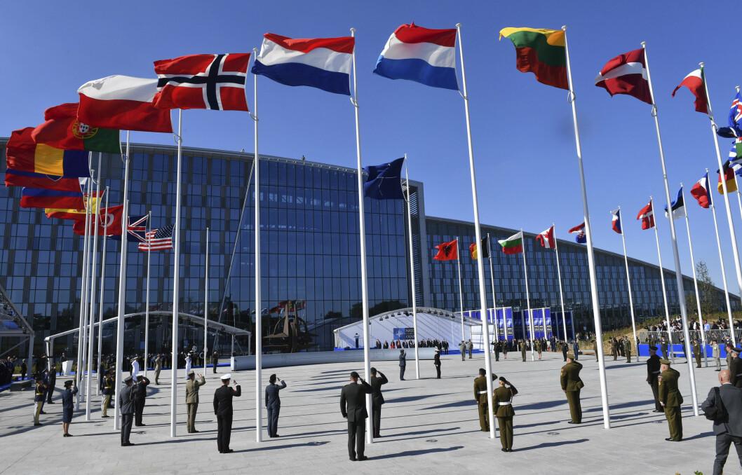 HOVEDKVARTERET: Utenfor den karakteristiske bygningen som huser Natos hovedkvarter i Brussel, vaier medlemslandenes flagg i vinden.